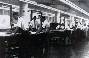 1950's: photo showing 7 or 8 men standing, working 2 to a table, simultaneously constructing the 850 mb, 700 mb and 300 mb upper air analysis charts in an assembly line fashion.